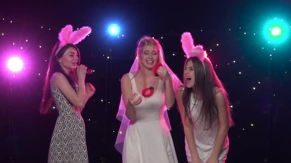 Cover Image for Bride Holding Sexy Gifts with Girlfriends Bachelorette Party. Slow Motion