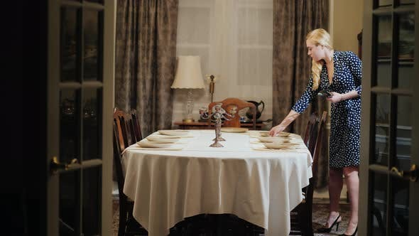 The Young Housewife Unfolds the Tableware. Serves the Table for Dinner