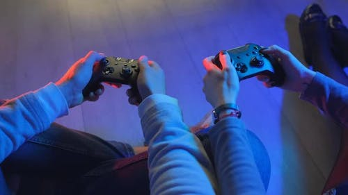 Hands of a Man and Girl Holding a Joysticks To Play Video Games on TV. Hands of a Players with a
