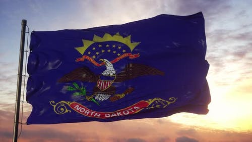 Flag of North Dakota Waving in the Wind Against Deep Beautiful Sky at Sunset