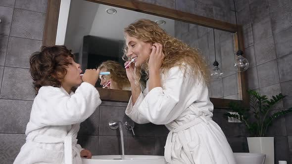 Thumbnail for Mother and Her Nice Son Dressed in Robes Brushing their Teeth Together