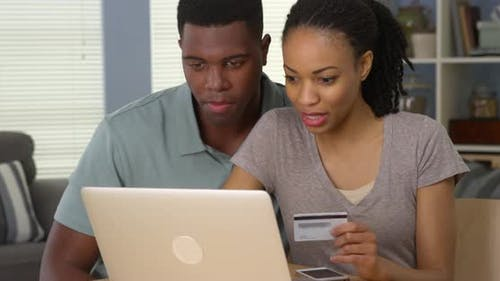 Happy African American man and woman making online purchase with credit card