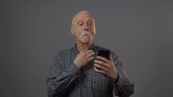 Thumbnail for Man Holds Telephone Looks at Screen and Straightens Shirt
