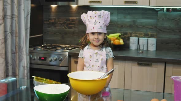 Little girl wearing an apron and a toque