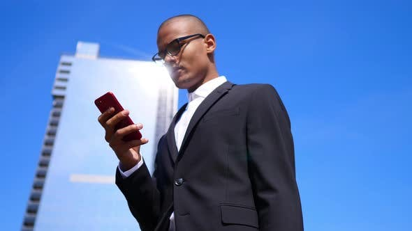 Thumbnail for Mixed-Race Businessman Using Smartphone And Smiling At Business Office Building.