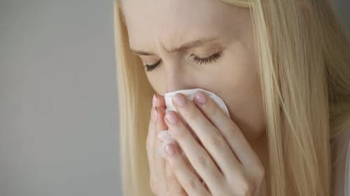 Sad Woman Wipes Her Nose with a Handkerchief Closeup