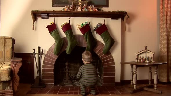 Thumbnail for Toddler in pajamas looking for Santa in the fireplace at Christmas
