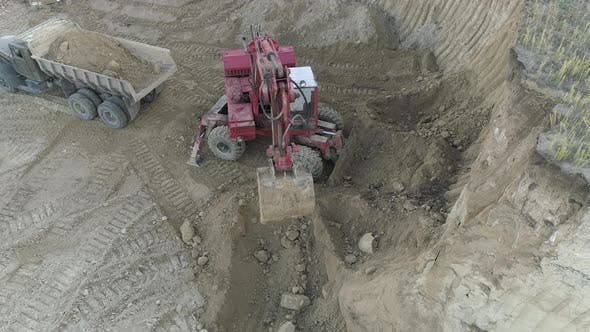 Thumbnail for Aerial view of an excavator digging soil