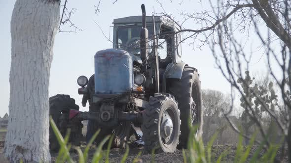 Thumbnail for Old Grey-haired Caucasian Farmer Walking Behind Tractor on Sunny Day