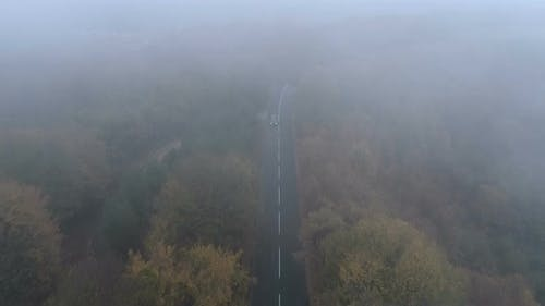 Aerial View of Black SUV with Turned Headlights Driving Along Spooky Foggy Road