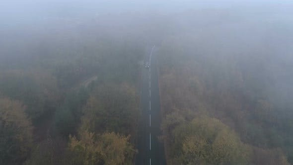Aerial View of Black SUV mit gedrechselten Scheinwerfern Fahren entlang Spooky Foggy Road