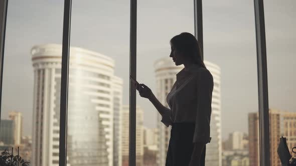 Thumbnail for Businesswoman Silhouette with a Mobile Phone in Hand. Girl Uses a Smartphone in the Office