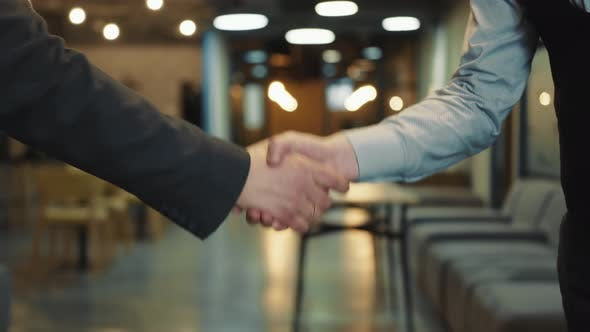 Close Up of Two Businessmen Greeting or Shaking Hands As a Sign of Successful Completion of Meeting