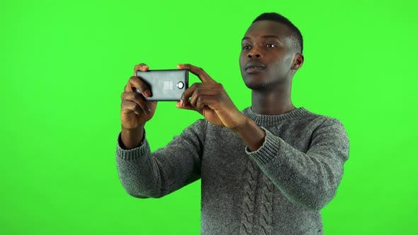 Thumbnail for A Young Black Man Takes Pictures of Something Off the Camera with a Smartphone - Green Screen Studio