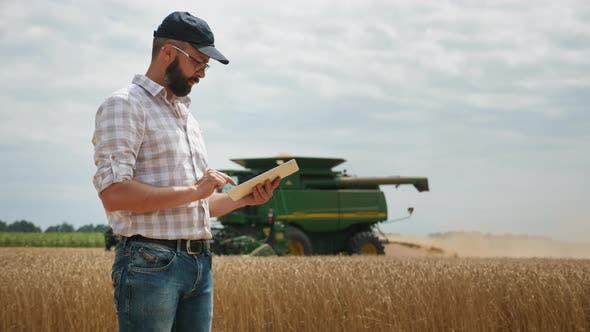 A Farmer Uses a Digital Tablet, in the Background Is a Harvester