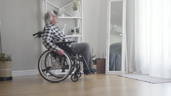 Thumbnail for Side View of Upset Elderly Caucasian Man in Wheelchair Rolling To Window at Home. Depressed Old