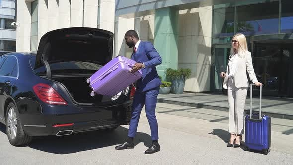 Man Puts Luggage in a Car