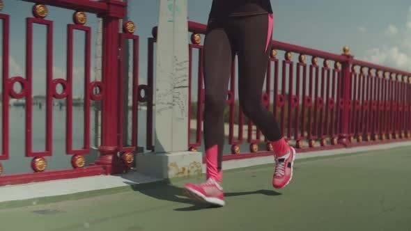 Thumbnail for Fit Female Athlete Running Along Urban Bridge