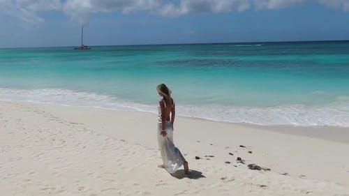 Woman in White Dress is Walking on a Tropical Beach Light Blue Ocean Water