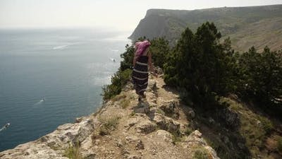 Girl with Pink Hair Walks Along Cliff Edge