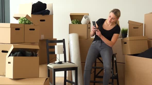 Thumbnail for A Moving Woman Sits on a Chair in an Empty Apartment and Takes Pictures of a Lamp on Another Chair