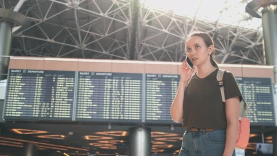 Cover Image for Girl Traveler at the Airport To Talk on a Mobile Phone