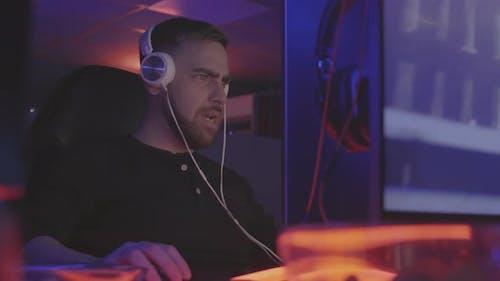 Gamer in Headphones Playing Online Shooter