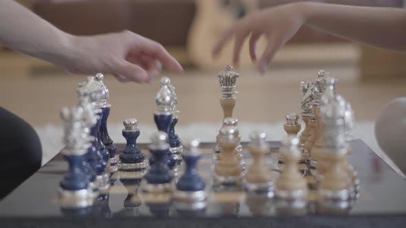 Thumbnail for Zwei Unerkennbare Menschen spielen schönes Luxusschach im Wohnzimmer in gemütlicher Atmosphäre