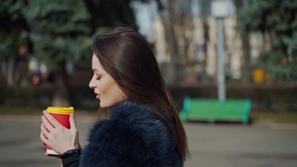 Thumbnail for Hübsches Mädchen mit heißem Getränk im Freien