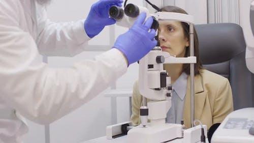 Senior Optometrist Examining Retina of Female Patient with Slit Lamp