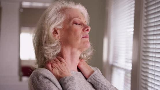 Close-up of elder woman with chronic neck pain looking out window worried