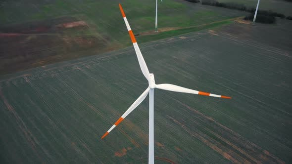 Top View Drone Tilts Down Directly Above Windmill Turbine with Red Blade Stripes, Alternative Energy