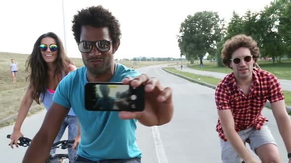 Thumbnail for Three young adults having fun cycling and taking selfies