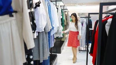 Asian Woman Walking Among Aisles at Fashion Store