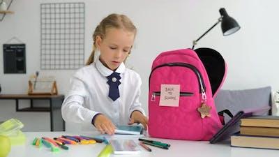 Girl Preparing Backpack with School Supplies