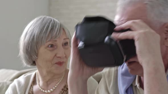 Thumbnail for Curious Elderly Couple Inspecting VR Goggles