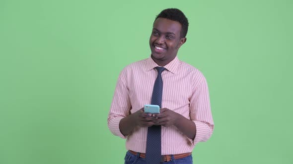 Cover Image for Happy Young African Businessman Thinking While Using Phone