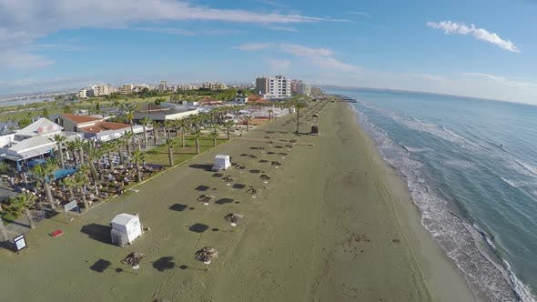 Thumbnail for Aerial view above empty beach with straw parasols, coastline in Larnaca, Cyprus