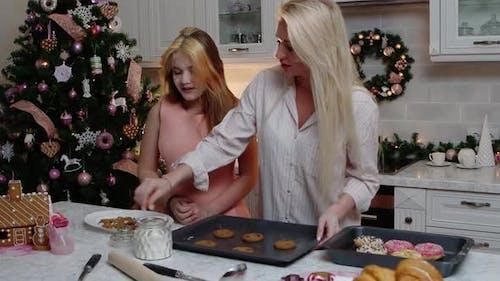 Familienweihnachtsmutter und ihre Tochter, die Kekse backen und Mehl auf die Kekse streuen
