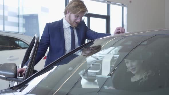 Thumbnail for Happy Man and Woman Discussing Which Car To Buy in Modern Motor Show. Woman Gives Tablet To Husband