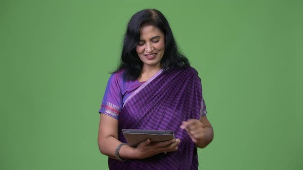 Thumbnail for Mature Happy Beautiful Indian Woman Smiling While Using Digital Tablet