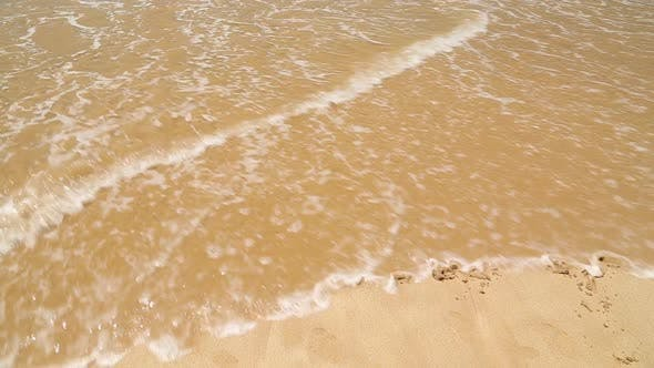 Thumbnail for HOLIDAY written in the beach sand washed aways by waves.
