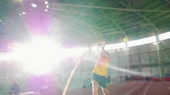 Thumbnail for Pole Vaulting Training - a Man in Yellow Shirt Performing a Jumping Over the Bar in the Indoors
