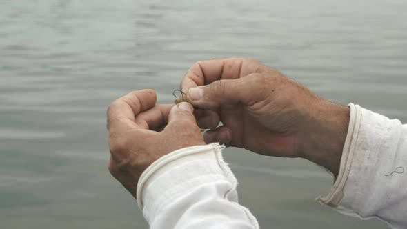 Close up of male hands with fishing gear. Fisherman preparing fishing bait for fishing.