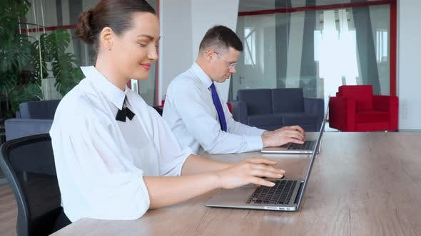 Thumbnail for Businessman and Businesswoman Working with Laptop