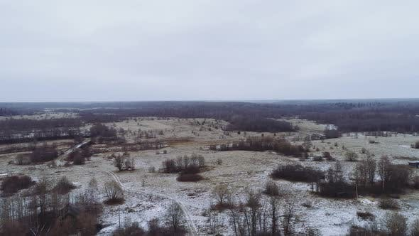 Flight Over the Winter Flat Landscape. A Rare Forest Between Large Meadows. Winter, Some Snow
