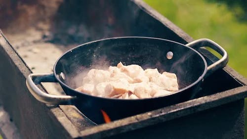 Close-up, Slow Motion: Pork Meat Is Fried in Saucepan on Charcoal
