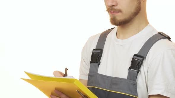 Beschnittene Aufnahme eines Industriearbeiters lächelnd Notizen auf der Zwischenablage machen