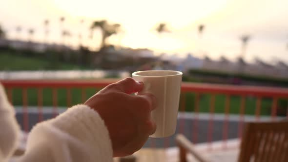 Female Hand Holding Hot Coffee Cup At Sunrise.