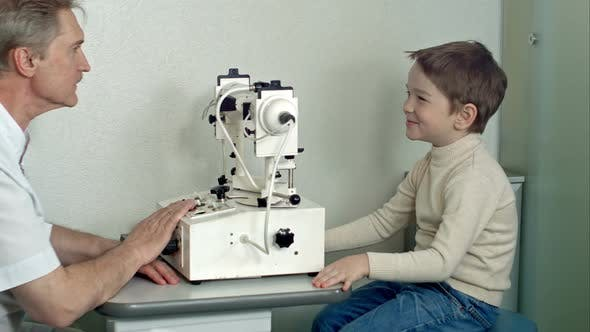 Cover Image for Ophthalmologist in Exam Room with Little Boy Sitting in Chair Looking Into Eye Test Machine